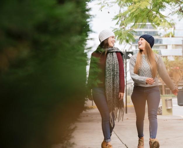 Duas mulheres sorridentes andando no parque