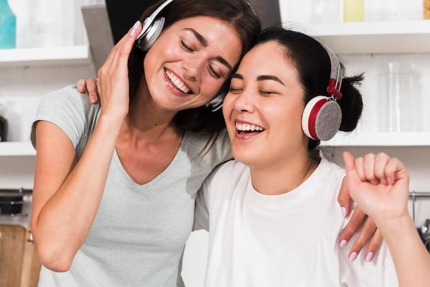 Duas mulheres sorridentes cantando música em fones de ouvido