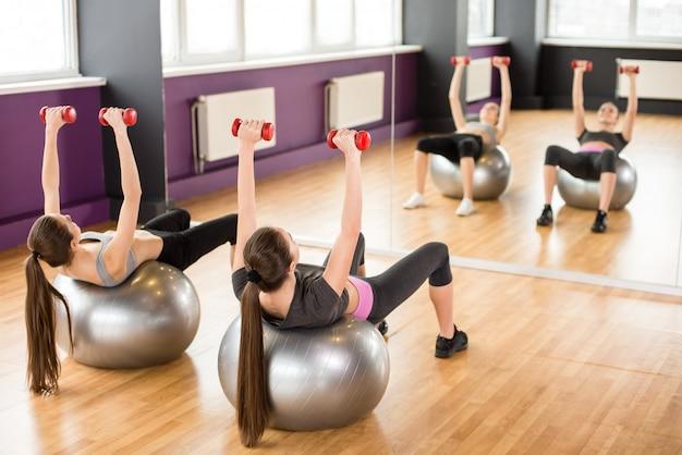 Duas mulheres sorridentes com bolas de exercício e halteres.
