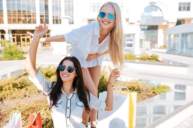 Duas mulheres sorridentes e felizes se divertindo enquanto estão sentadas no banco após as compras
