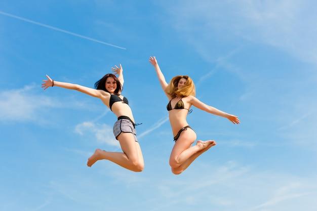 Duas mulheres sorridentes em trajes de banho pulando alto no céu