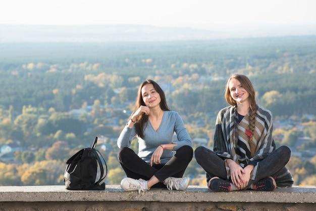 Duas mulheres sorridentes, sentado em uma colina, floresta de outono à distância
