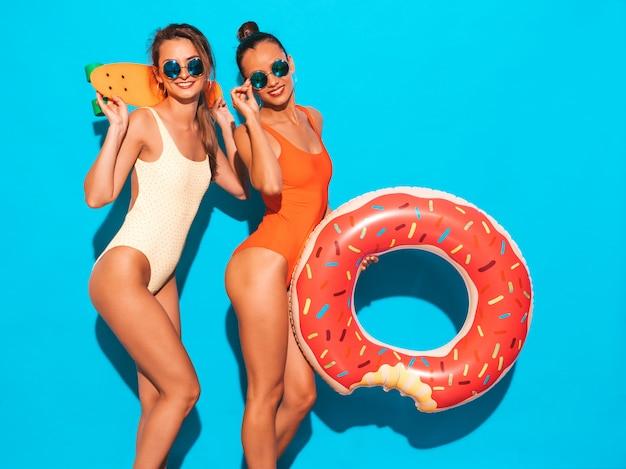 Duas mulheres sorridentes sexy bonitas em trajes de banho swimwear colorido de verão. garotas de óculos escuros. modelos positivos se divertindo com skates centavo coloridos. com colchão inflável donut lilo