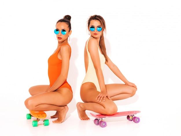 Duas mulheres sorridentes sexy bonitas em trajes de banho swimwear colorido de verão. meninas da moda em óculos de sol. modelos positivos, sentado no chão com skates centavo coloridos. isolado