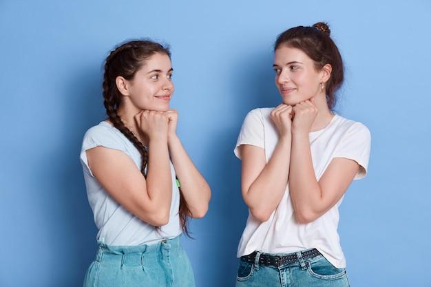 Duas mulheres tímidas amigas europeias em roupas casuais posando isoladas sobre uma parede azul