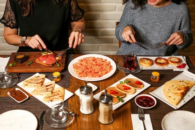 Duas mulheres tomam café da manhã com torradas, crepes, panquecas, geléia e ovos mexidos