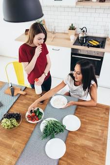 Duas mulheres tomando café da manhã em casa na cozinha.