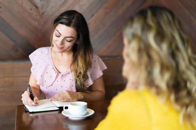 Duas mulheres tomando café e fazendo anotações no café