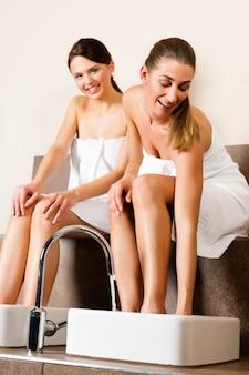 Duas mulheres tomando um banho de pé