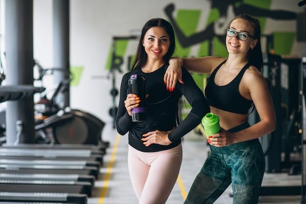 Duas mulheres treinando juntos na academia