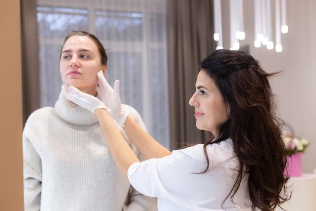 Duas mulheres, uma esteticista e uma cliente, estão em frente ao espelho, em uma consulta, discutindo os próximos procedimentos. esteticista fala sobre esculpir o rosto