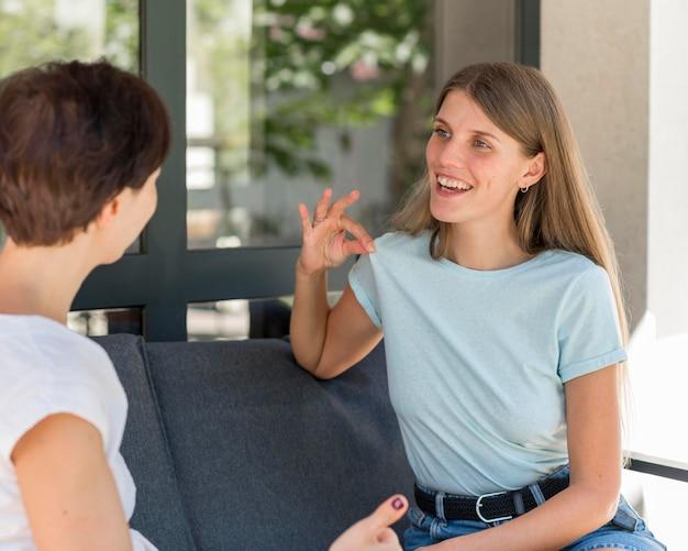 Duas mulheres usando linguagem de sinais para conversar uma com a outra