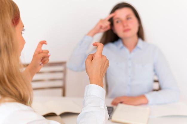 Duas mulheres usando linguagem de sinais para conversar