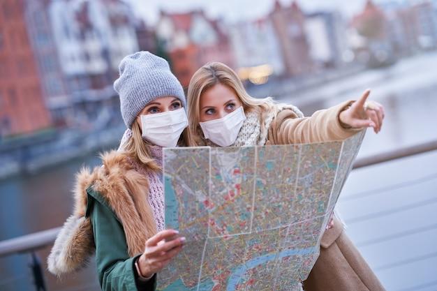 Duas mulheres usando máscaras e segurando um mapa enquanto visitam gdank, na polônia