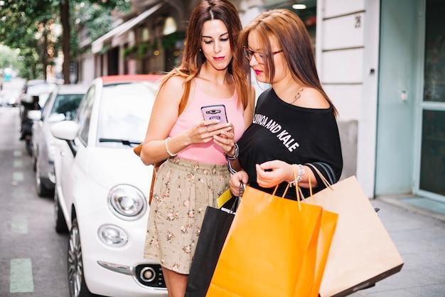 Duas mulheres usando o telefone perto do carro
