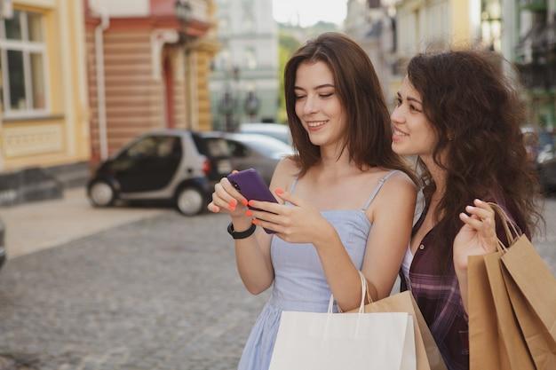 Duas mulheres usando telefone inteligente, andando na cidade depois de fazer compras juntos