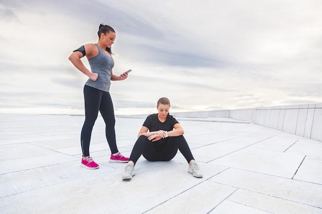 Duas mulheres verificando estatísticas de treino em seus dispositivos electônicos