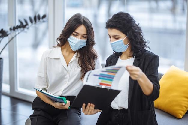 Duas mulheres verificando gráficos e discutindo tendências de negócios no escritório.