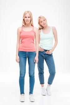 Duas mulheres vestidas com camisetas e jeans posando. isolado sobre a parede branca. olhando para a frente