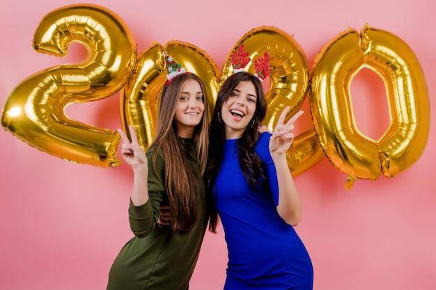 Duas mulheres vestindo aro de natal e abraçando na frente de balões de ouro 2020 isolados sobre rosa