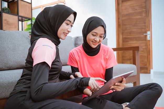 Duas mulheres vestindo roupas de ginástica hijab, sentadas relaxadas no chão enquanto usam um tablet digital e tocam a tela do tablet com os dedos enquanto se recostam no sofá em casa