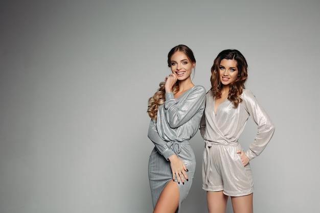 Duas mulheres vestindo roupas elegantes, preparando-se para a festa de natal.
