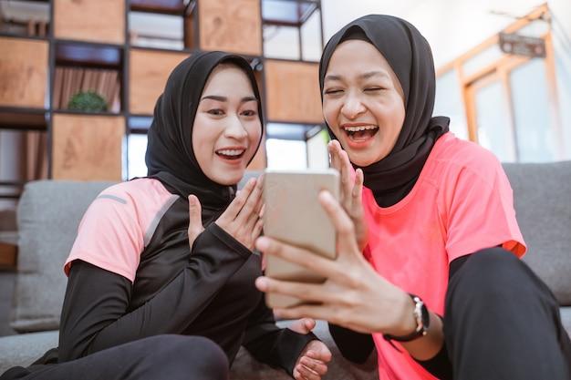 Duas mulheres vestindo roupas esportivas hijab riem enquanto leem mensagens juntas em um celular enquanto estão sentadas no chão da casa