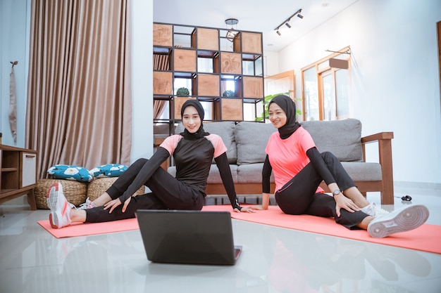 Duas mulheres vestindo roupas esportivas hijab sentadas no chão enquanto aquecem os quadris juntas em casa