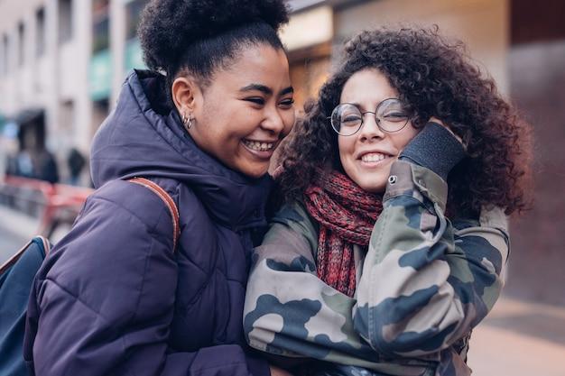 Duas mulheres youg abraçando na rua
