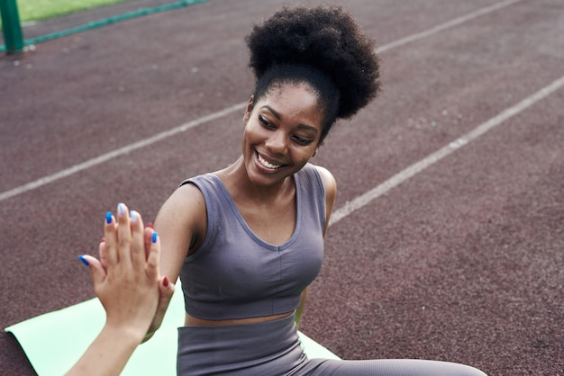 Duas namoradas africanas e iranianas se dão cinco durante o exercício. mulheres jovens de esportes torcendo juntos ao ar livre para aulas de ginástica na rua. fechar-se.