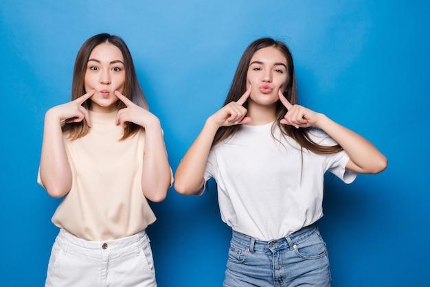Duas namoradas apontando para as bochechas isoladas na parede azul