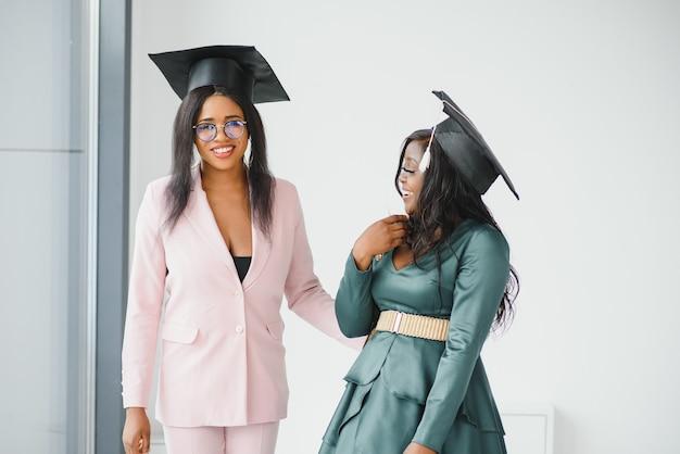 Duas namoradas asiáticas e afro-americanas jovens alegres em vestes de formatura, tirando selfie, mostrando diplomas e sorrindo para a câmera, closeup retrato sobre o campus universitário