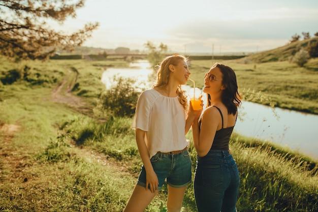 Duas namoradas bonitas bebem suco de laranja com palha ao pôr do sol, em óculos de sol, expressão facial positiva, ao ar livre