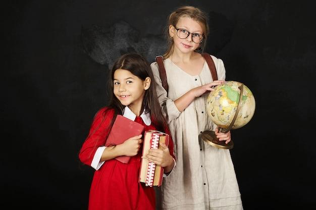 Duas namoradas bonitas de alunas em pé perto de um quadro-negro com livros