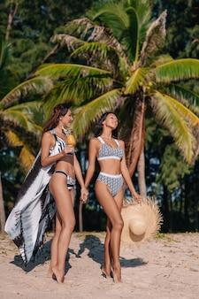 Duas namoradas de biquíni da moda dão as mãos uma da outra relaxante praia com suco fresco. estilo de moda, tendências jovens, idéia moderna de roupas de lazer. esportes figuras bronzeadas mulheres