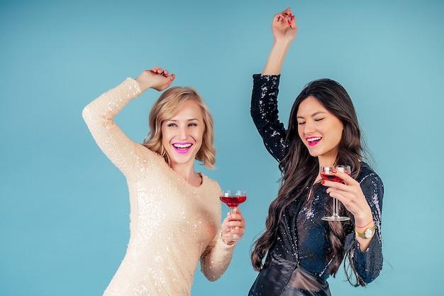 Duas namoradas felizes e atraentes, morenas e loiras com vestido de lantejoulas brilhantes à noite, segurando uma taça de vinho e dançando em uma festa no estúdio sobre um fundo azul