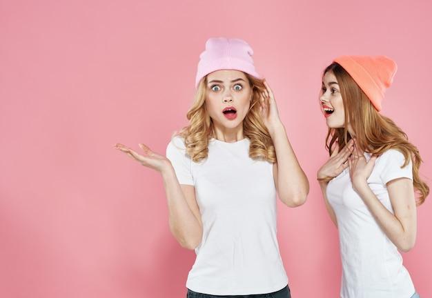 Duas namoradas glamorosas em camisetas coloridas chapéus comunicação fundo rosa