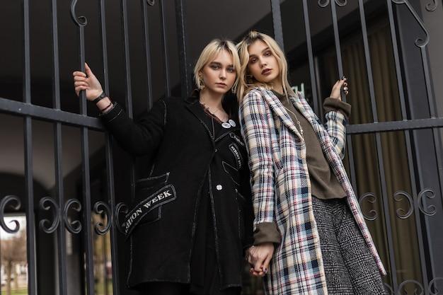 Duas namoradas jovens e elegantes loiras em jaquetas elegantes enormes posando perto do portão de ferro na rua