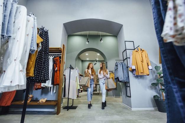 Duas namoradas jovens e lindas estão andando em um estilo de showroom de loft coisas elegantes com sacolas de presente, sorrindo uma para a outra.