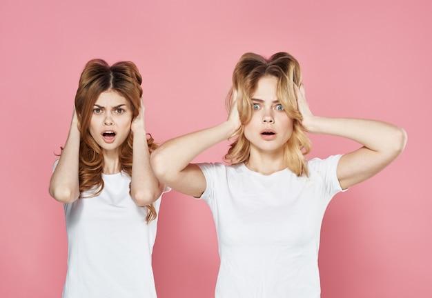 Duas namoradas jovens em camisetas brancas cortadas vista de fundo rosa