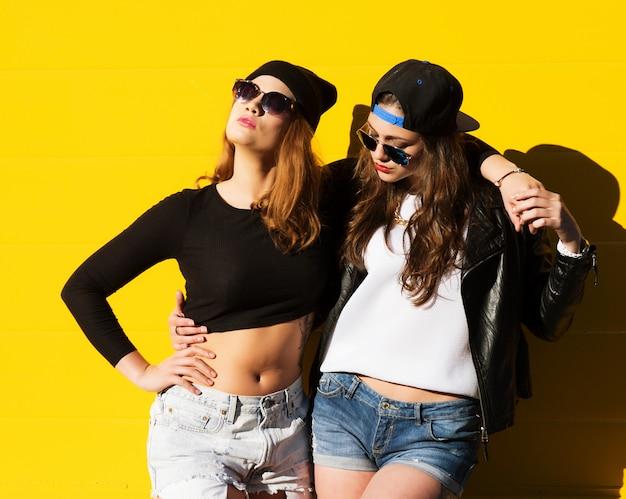 Duas namoradas jovens em óculos de sol se divertindo.