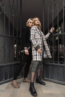 Duas namoradas jovens loiras na moda em jaquetas elegantes enormes e botas de couro vintage posando perto do portão de ferro na rua