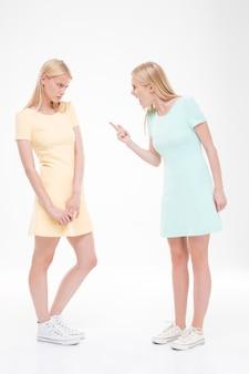 Duas namoradas juram. isolado sobre a parede branca.