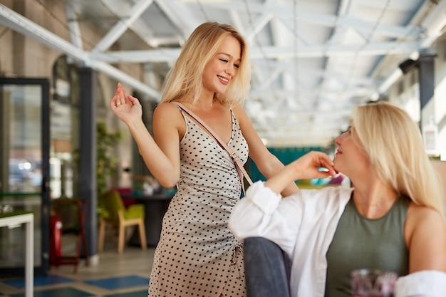 Duas namoradas loiras caucasianas se cumprimentando em um restaurante moderno