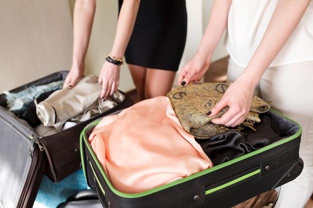 Duas namoradas pegam uma mala em um quarto de hotel.