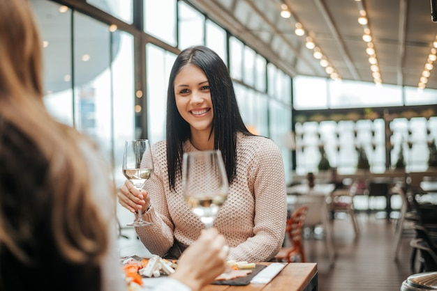 Duas namoradas que bebem o vinho no café e na fala.
