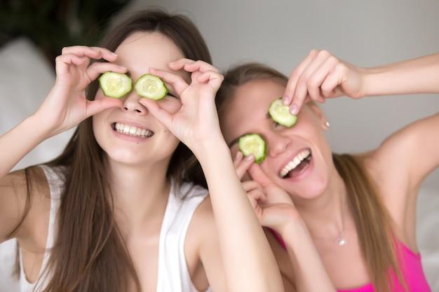 Duas namoradas sendo bobo, colocando pepinos em seus olhos.