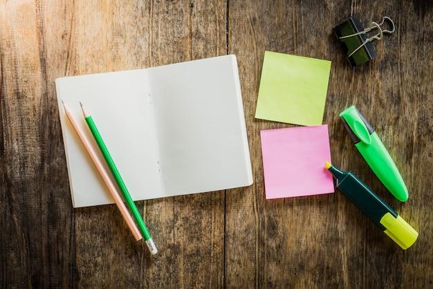 Duas notas auto-adesivas coloridas em branco, caderno, lápis, caneta de marca-texto, clip
