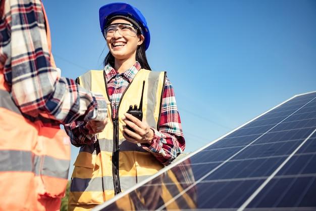 Duas operárias asiáticas segurando um tablet e controlando a instalação de pesados painéis solares fotovoltaicos em uma plataforma alta de aço em um campo de milho