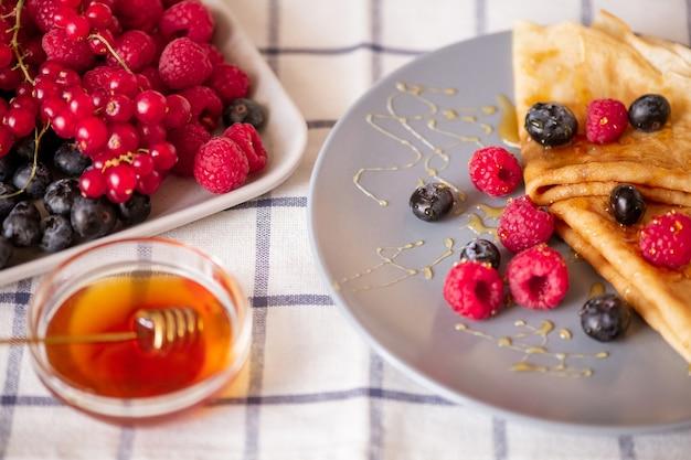 Duas panquecas caseiras dobradas com mel e framboesas frescas maduras e amoras no prato de porcelana cinza na mesa da cozinha
